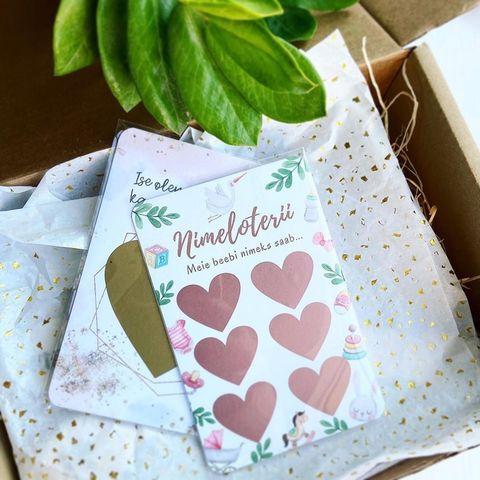 Roosa kujundusega beebi nimeloterii kaart pakendis